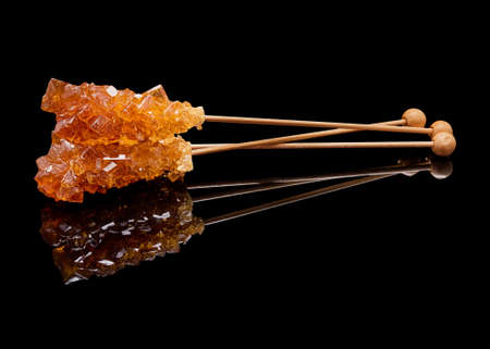 Three lying sticks of brown sugar with a real reflection on a black glossy background