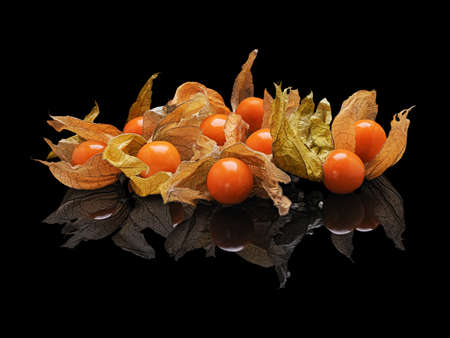 Heap berries of the plant Physalis isolated on black glossy background with real reflection. Stock Photo