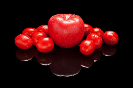 One big whole red and a pile of small tomatoes isolated on black glossy background with real reflection. Side view
