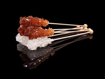 Set lying sticks of brown and white sugar with real reflection on a black glossy background