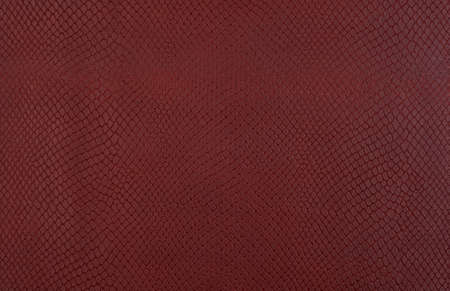 Brown embossed imitation snake skin background Фото со стока