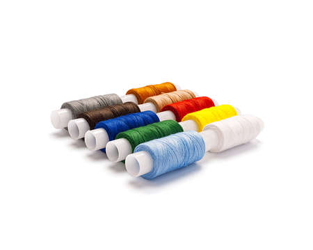 Set of multi-colored spools of cotton thread lying diagonally isolated with real shadow. Side view