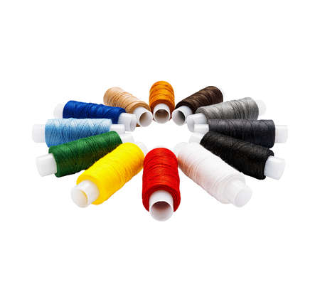 Set of multi-colored cotton threads on plastic spools arranged in a circle isolated. Side view