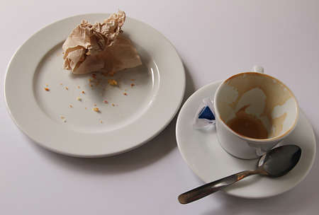breackfast: Leftovers from breackfast: empty cup and plate and balled up napkin.