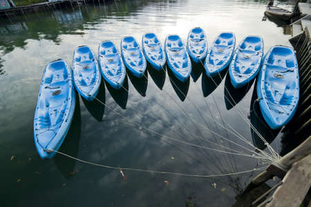 fibreglass: kayaks de fibra de vidrio de color azul amarrado a un muelle Foto de archivo