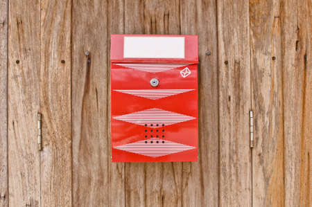 Red mailbox on old wood wall photo
