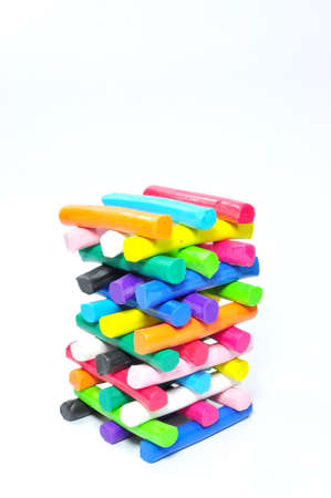 Stack of colorfull plasticine on white background photo