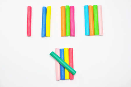 colorful plasticine stick counted on white background photo