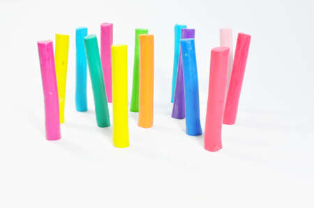 Colorful plasticine stick stand on white background photo