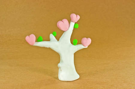 Tree of love made from plasticine pink heart white trunk green leaves on brown paper background photo