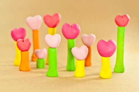 group of sweet color heart on post made from plasticine on brown paper background Stock Photo - 14606111