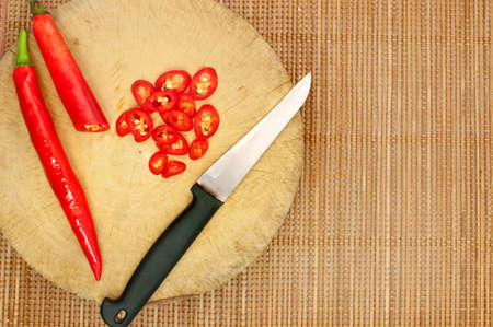 Knife and red chilli on cutting board , cooking concept photo