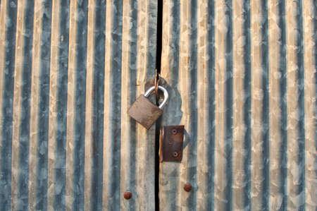 Closed wave metal door with metal lock Stock Photo - 14843773