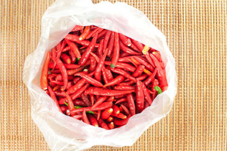 Red chilli in plastic bag on bamboo mat  photo