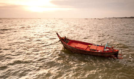A small wooden fishing boat  floating in the sea photo