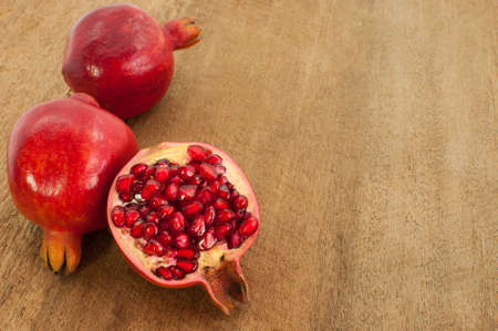 group of pomegranate isolated on wood background photo