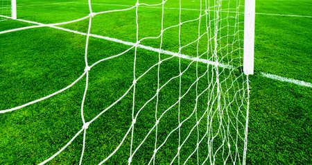 soccer net: soccer net on green grass, view from behide the goal line