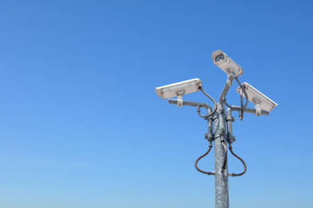 Three outdoor security cameras with housing on the pole cover multiple angles