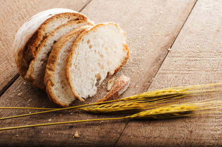 sliced bread and wheat on the wooden table photo