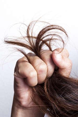 Woman hand grabbed damaged hair