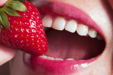 Macro close up of a beautiful female mouth eating a fresh strawberry Stock Photo