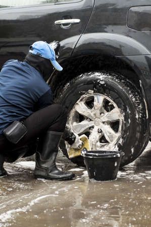 A man washing the car tire Stock Photo