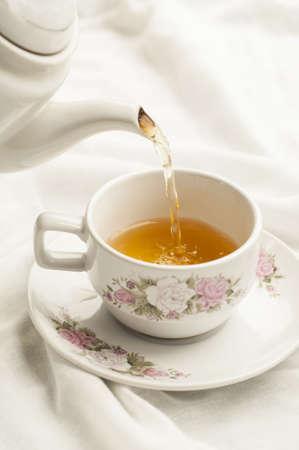 kettles: T� que se vierte en la taza de t� en el fondo de tela blanca Foto de archivo