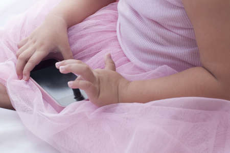 child finger: Girl touching smart phone with her cute hand