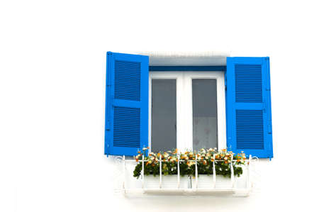blue window on a white wall with flower decoration photo