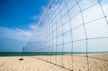 Torn beach volleyball net at tropical beach photo