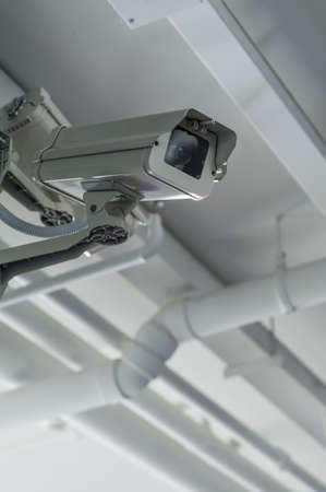 under surveillance: Security camera on the ceil with housing Stock Photo