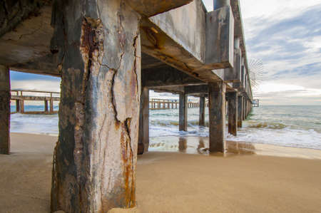 Corrosion concrete, Concrete pier corrosion agains the sea Stock Photo