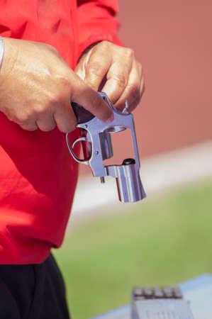 reloading: Red shirt man reloading ammo to silver gun
