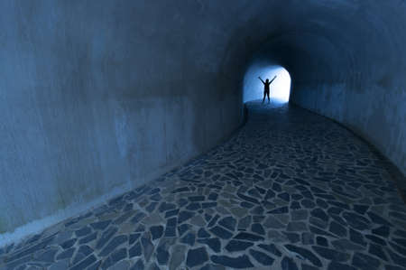 silhouette of man at end of tunnel photo
