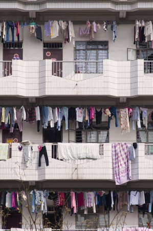 Many clothes hanging over balcony at Chinese dormitory, apartment  報道画像