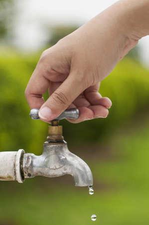 llave de agua: Mano de la mujer cerr� la llave de agua, prevenir el escape de residuos