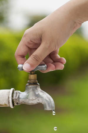 Woman hand shut the faucet, prevent from leaking waste photo