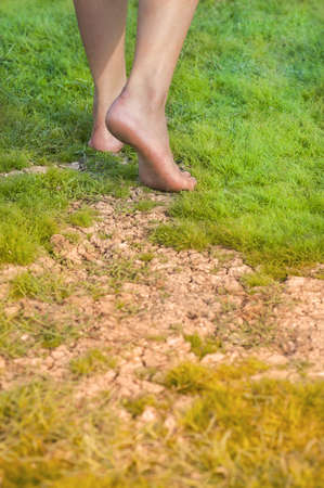 Barefoot walking from dry land to green land
