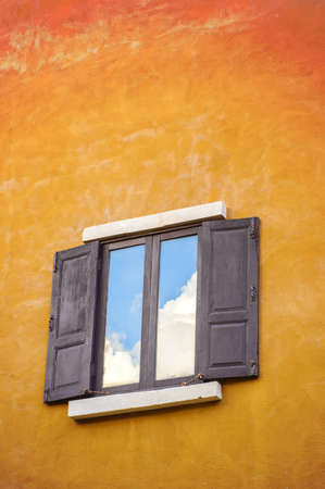 Sky reflex on window at hot old yellow wall,summer concept photo