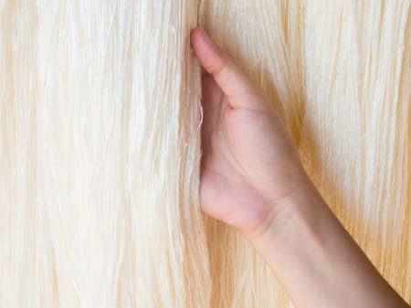 mano que sostiene la seda cruda