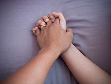 Two hands of lover clasp on bed