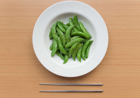 leguminosae: Stir fired fresh Sugar snap pea on table with chopsticks