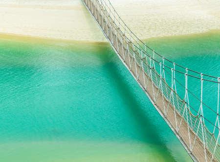 Suspension Bridge crosses blue canal Stock Photo