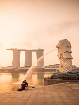 Lovers sat in front of the Merlion at Marina bay, Singapore