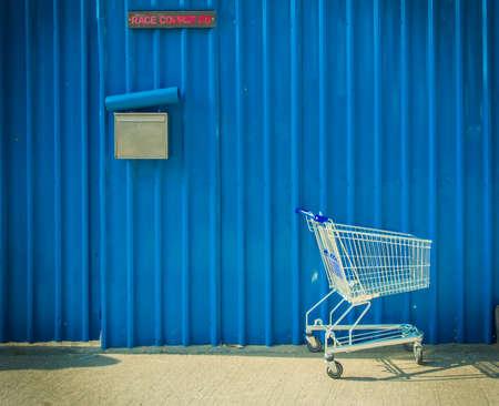 青い金属シートの背景が付いている通りの横にあるショッピング カートのまま 写真素材 - 27506999