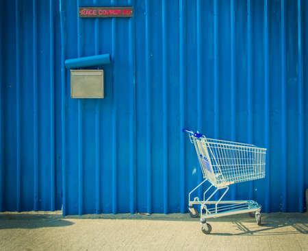 home shopping: Shopping cart leave beside the street with blue metal sheet background
