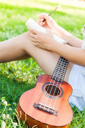 Female song writer. Write in notebook with little guitar on her side Stock Photo