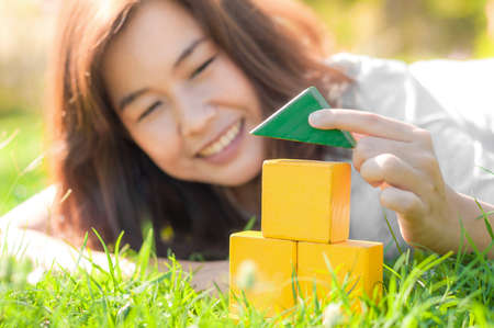 Woman playing mini house model in the garden  Home dreaming concept photo