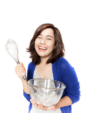 asian people: Isolated portrait of beautiful young success woman with whisk and flavor bowl on white background. Pretty female model smiling happy. Stock Photo