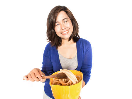 Isolated portrait of young happy woman preparing pasta on white background. Pretty female model happy smiling. photo